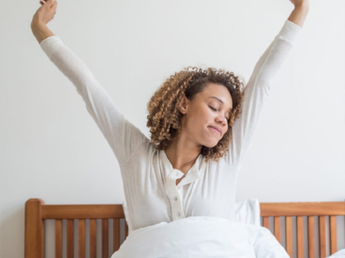 You won't believe the benefits of a good nights rest. Woman waking up refreshed.